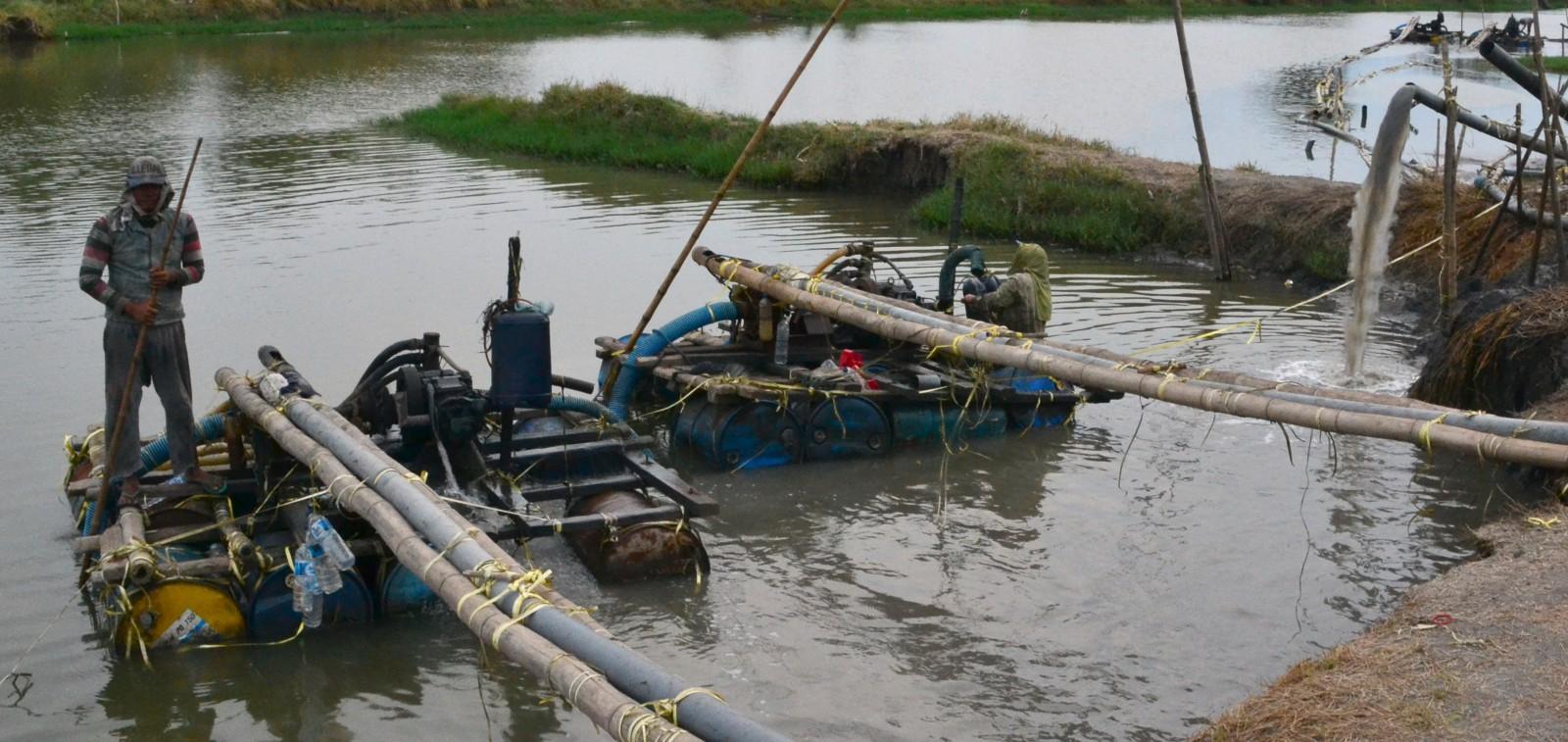 Skramliga motorer driver pumparna som flyttar sanden från bassänger till väntande lastbilar